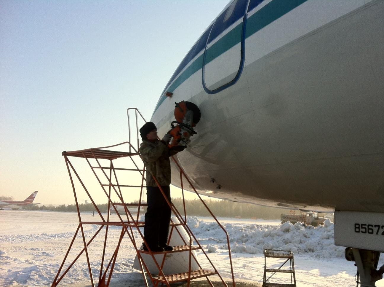 Процесс резки самолета для отделения кабины от фюзеляжа